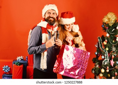 Christmas party concept. Man and woman with smiling faces on red background. Mister and Missis Claus hold glasses of champagne and pink shopping box. Santa and sexy girl receive presents near fir tree