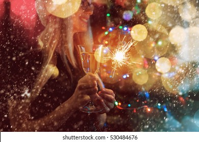 Christmas party girl with glass of champagne in the glare of the lights garlands