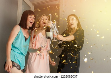 Christmas party. Incredible, sexy happy girls in silk pajamas drinking a champagne, making toast, on merry christmas night. Confetti. At home. Happy new year time, party with alcohol drinks
