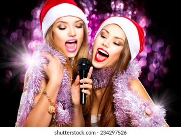 Christmas party, karaoke. Beauty girls in santa hat with a microphone singing and dancing over holiday blinking dark background. Disco. New year celebration