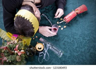 christmas party morning after, woman asleep on table with alcohol at christmas