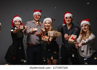 Christmas party, New Year celebration, sale, black friday, holiday, fun, togetherness. Group of happy smiling people with gift boxes confetti falling on the fore plane