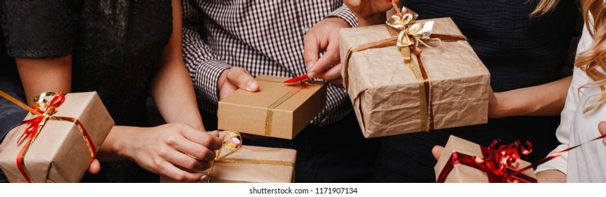 Christmas party, New Year celebration, sale, black friday, holiday, fun, togetherness. Group of people with presents. Close up hands opening gift boxes