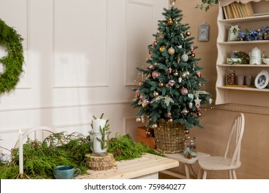 Christmas party table with branches of eve in living room. Empty room with Christmas decorations. Beautiful holiday table with decorations and Christmass tree. New Year holiday concept.