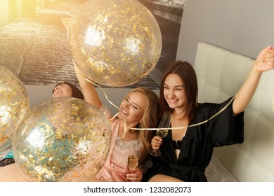 Christmas party. Three attractive cheerful young girls having fun, playing with balloons, drinking a champagne and having fun at merry christmas party in the bedroom. X-mas concept