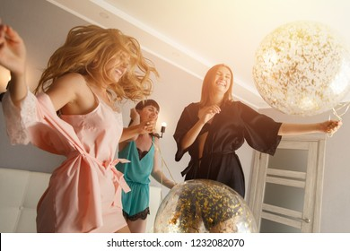Christmas party. Three attractive young women having fun while jumping on the bed, with balloons. Dressed up in silk pajamas. At home in merry christmas night