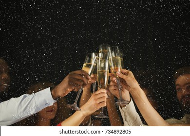 Photo of Christmas party time. Young people toasting with champagne flutes. Multiethnic friends congratulating each other with new year. Celebration and nightlife concept, holiday background, selective focus