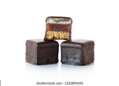 Christmas pastry, German gingerbread with cherry jelly and marzipan in chocolate called Dominosteine, isolated on a white background