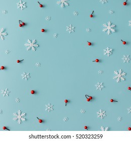 Christmas pattern made of snowflakes and red berries on blue background. Winter concept. Flat lay.