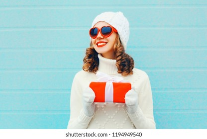 Christmas, people concept - happy smiling woman holds gift box in hands in knitted hat, sweater on blue background