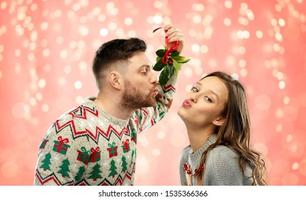 christmas, people and holiday traditions concept - portrait of happy couple in ugly sweaters kissing under mistletoe over festive lights on pink coral background
