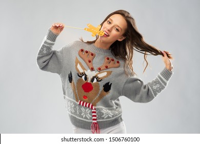 christmas, people and holidays concept - happy young woman wearing jumper with reindeer pattern and biting gingerbread party accessory at ugly sweater party