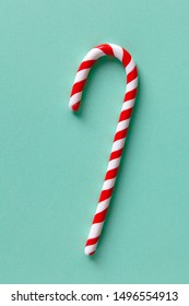 Christmas peppermint candy cane on pastel turquoise background. Festive minimal style flat lay. For greeting card, invitation, social media. Vertical.