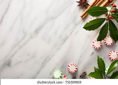 Christmas peppermint candy and spices on marble background