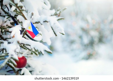 Christmas Philippines. Xmas tree covered with snow, decorations and a flag of Philippines. Snowy forest background in winter. Christmas greeting card.