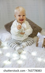 Christmas photo of cute 1 year old baby boy in cozy clothes, posing in New Year decorated room