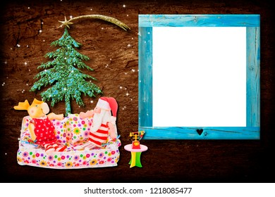 Christmas photo frame card. Santa Claus and the reindeer sitting on a sofa next to the phone and the Christmas tree on wooden background and with an empty frame for photos or messages