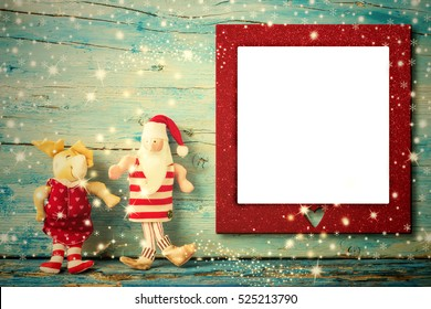 Christmas photo frame card, Santa Claus and reindeer rag dolls and empty photo frame with heart , vintage tone wooden background