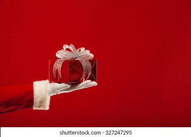 Christmas. Photo of Santa Claus gloved hand with red gift box, on a red background