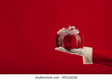 christmas Photo of Santa Claus gloved hand with giftbox, on a red backgro
