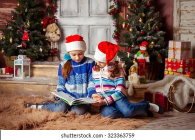 Christmas photo two girls sisters in elegant interior near the Christmas tree with gifts