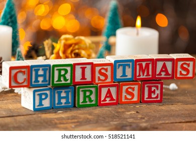 Christmas Phrase Written With Toy Blocks On Christmas Card Background.