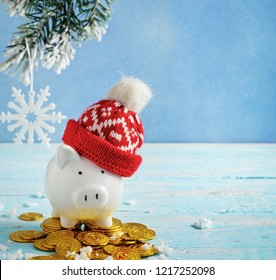 Christmas piggy bank in a hat with coins on blue