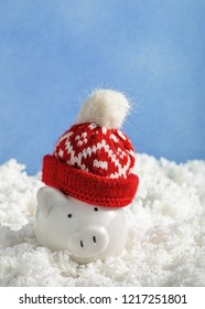 Christmas piggy bank in a hat in fake snow decoration