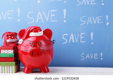 Christmas piggy bank next to some gift boxes and the word SAVE!  written several times on a blue background