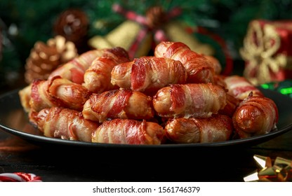 Christmas Pigs in blankets, sausages wrapped in bacon with decoration, gifts, green tree branch on wooden rustic table