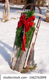 Christmas pine bough with bright red bow on retro wooden sled in snow