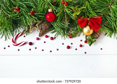 Christmas pine tree with decoration, red berries, balls, candy cane, cones on a white wooden background. Christmas greeting card. Text space.