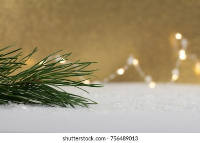 christmas pine twig on white in front of golden glittering background