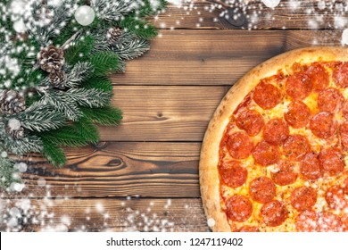 Christmas pizza pepperoni decoration snowflake on brown wood board.