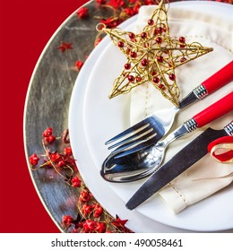 Christmas place setting, isolated on a red background