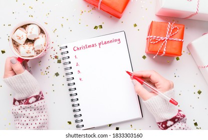 Christmas Planning Background. Female hand writing to-do list in notebook, cup of hot cocoa with marshmallows, holiday gifts and confetti decorations flat lay on white table, top view above shot
