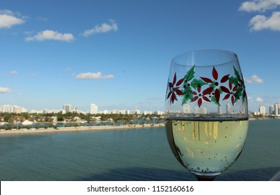 Christmas poinsettia themed crystal goblet stemware holds white wine with port of Miami, sea, blue sky, and fluffy clouds on horizon in background.