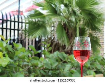 Christmas poinsettia themed crystal goblet stemware in foreground holds red wine with palm tree and decorative iron fence in background.
