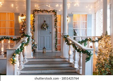 Christmas porch decoration idea. House entrance decorated for holidays. Golden and green wreath garland of fir tree branches and lights on railing. Christmas eve at home. - Shutterstock ID 1851425764