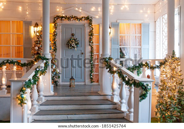 Christmas porch decoration idea. House entrance decorated for holidays. Golden and green wreath garland of fir tree branches and lights on railing. Christmas eve at home.
