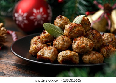 Christmas Pork stuffing meatballs with sage and onion. decoration, gifts, green tree branch on wooden rustic table