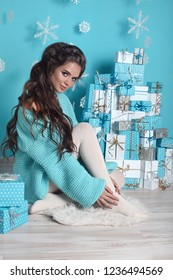 Christmas Portrait of attractive pretty woman with long wavy hair style. Beautiful brunette girl wears in turquoise knitted woolen sweater over Christmas gifts boxes and xmas decorations.