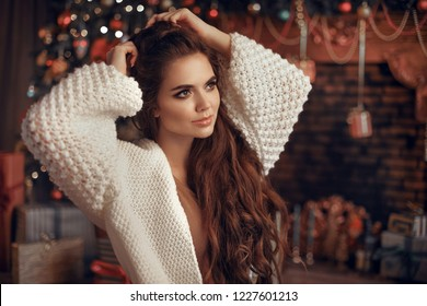Christmas portrait of attractive woman with knitted sleeves. Beautiful brunette girl with long hair style wears in warm white woolen sweater over Christmas tree and xmas decorations.