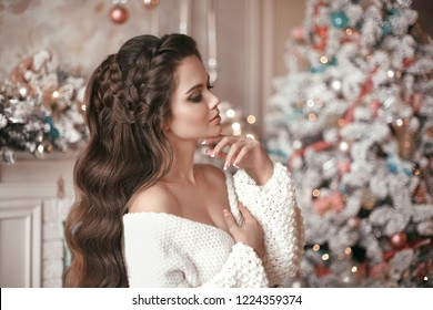 Christmas portrait of attractive woman with wedding hairstyle. Beutiful brunette girl with long hair style wears in warm white woolen sweater over Christmas tree and xmas decorations.