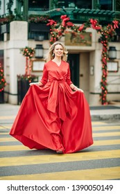 Christmas portrait of beautiful woman with blond hair, wearing long red dress, walking down the street
