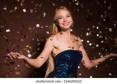 christmas portrait of beautiful woman smiling on brown background with golden confetti