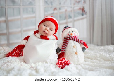 Christmas portrait of cute little newborn baby boy, wearing santa hat and  little cute snowman toy, studio shot, winter time
