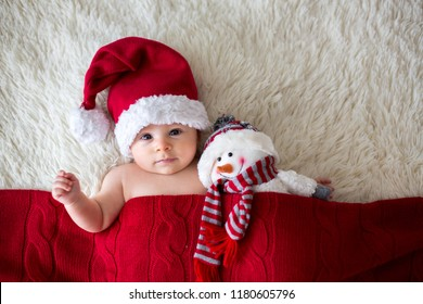 Christmas portrait of cute little newborn baby boy, wearing santa hat and hugging little cute snowman toy, studio shot, winter time