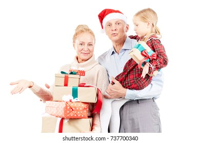 Christmas portrait of grandparents and granddaughter posing with gifts