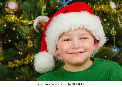 Christmas portrait of happy child wearing Santa hat in front of Christmas tree